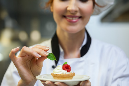 pastry chef: Smiling head chef putting mint leaf on little cake on plate in professional kitchen