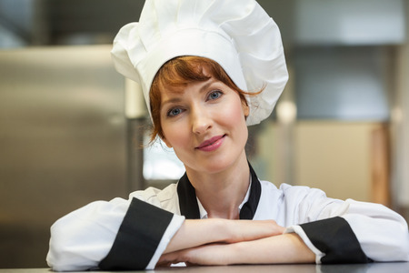 Pretty smiling head chef looking at camera in professional kitchen photo