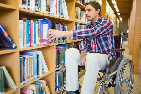 Man in wheelchair selecting book from bookshelf in the library photo