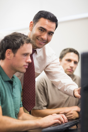 Portrait of smiling teacher showing something on screen to mature student in the computer room photo