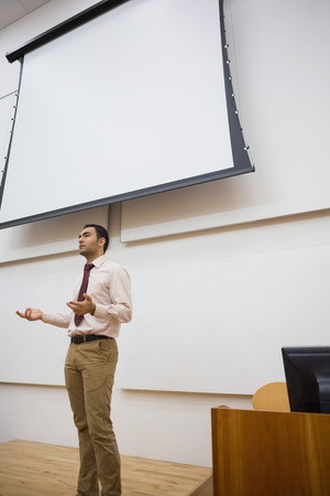 lecturing hall: Elegant male teacher standing against projection screen in the lecture hall