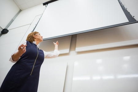 lecturing hall: Low angle view of an elegant female teacher with projection screen in the lecture hall