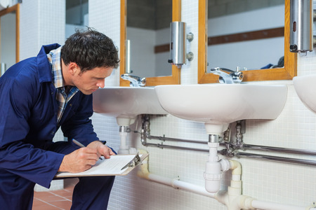 boiler suit: Handsome plumber looking at sink holding clipboard in public bathroom