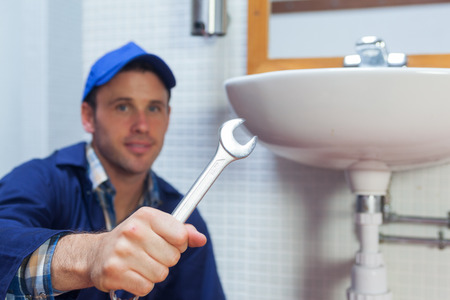 Handsome smiling plumber showing wrench in public bathroom photo