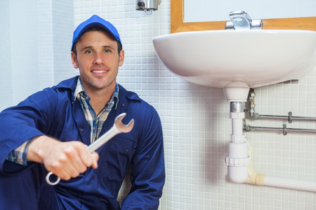 boiler suit: Happy plumber holding wrench sitting next to sink in public bathroom Stock Photo