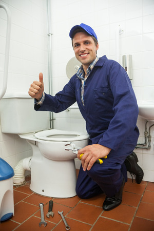 Plumber kneeling next to toilet showing thumb up in public bathroom photo