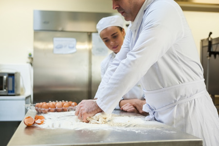 Serious head chef kneading dough in professional kitchen photo