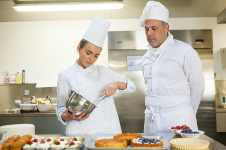 pastry chef: Serious chef whisking while being watched by head chef in professional kitchen