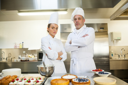 Serious chef and head chef standing arms crossed in professional kitchen photo