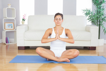 Front view of meditating slim woman sitting in lotus position on exercise mat in her living room photo