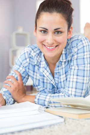 assignments: Portrait of cheerful gorgeous student lying on the floor doing assignments in the living room Stock Photo