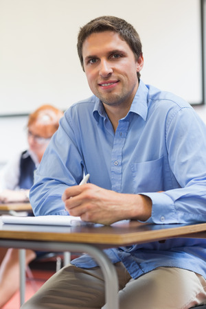Portrait of a mature student taking notes with others in lecture in college photo