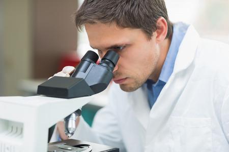 laboratory technician: Close-up of a male scientific researcher using microscope in the laboratory Stock Photo