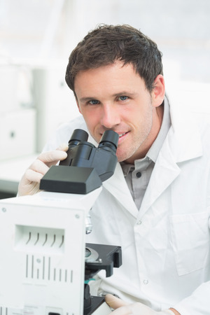 Close-up portrait of a male scientific researcher using microscope in the laboratory photo