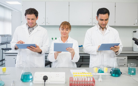 Group of serious scientists using tablet PCs in the laboratory photo