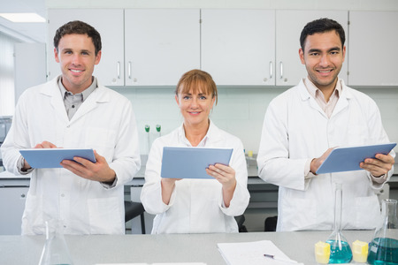 Group of smiling scientists using tablet PCs in the laboratory photo
