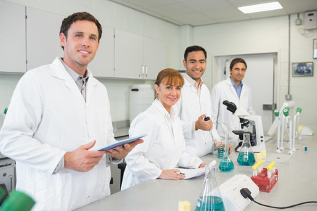 Group portrait of smiling scientists working in the laboratory photo
