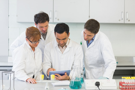 Group of serious scientists using tablet PC in the laboratory photo