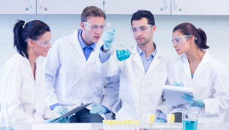 Group of scientists with tablet PC working on an experiment at the laboratory photo