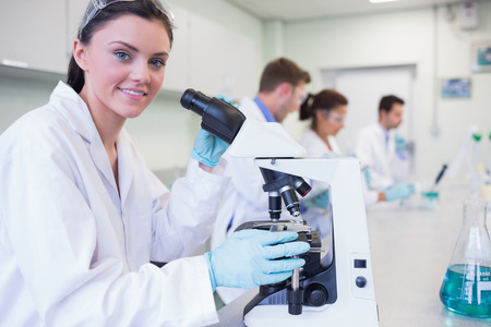 Portrait of a smiling female with researchers working on experiments in the laboratory photo