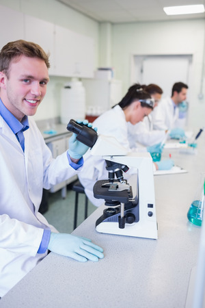 Portrait of a smiling male with researchers working on experiments in the laboratory photo