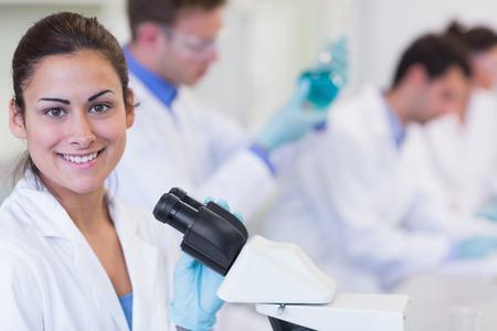研究室での実験に取り組んでいる研究者と笑顔の女性の肖像画