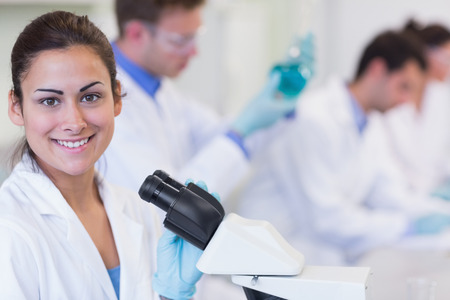 Portrait of a smiling female with researchers working on experiments in the laboratory Stock Photo