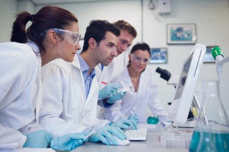 lab coat: Vista lateral de los investigadores serios mirando la pantalla del ordenador en el laboratorio Foto de archivo