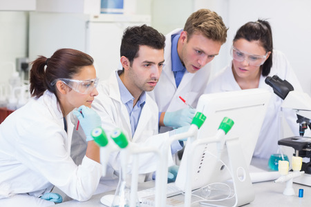 Group of scientific researchers looking at computer screen in the laboratory photo