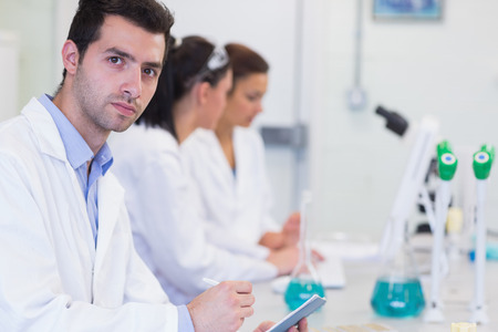 laboratory technician: Portrait of a male with researchers working on experiments in the laboratory Stock Photo