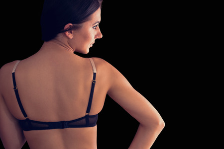 Rear view of gorgeous young woman wearing dark lingerie on black background photo