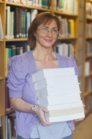 Mature female librarian posing holding a pile of books looking at camera photo
