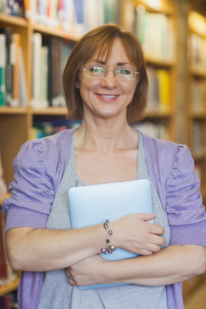 Mature female librarian posing in library holding a tablet smiling friendly at camera photo