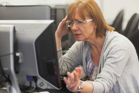 Angry mature student working with computer in computer class Stock Photo
