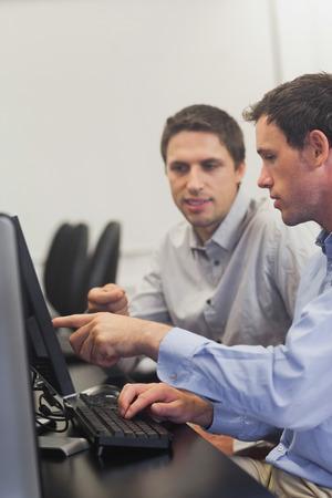 uomini maturi: Due uomini maturi che parlano, seduti davanti al computer a computer di classe