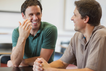 30s adult: Two friendly male mature students chatting while sitting in class room Stock Photo