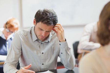 Concentrating handsome mature student sitting in classroom with classmates while learning
