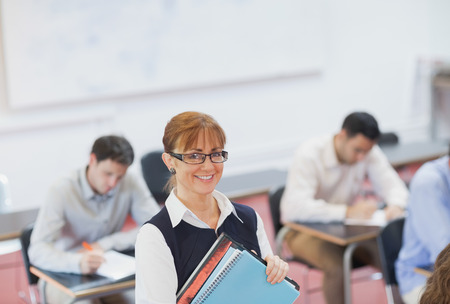 Female teacher posing in her classroom holding some files smiling at camera photo