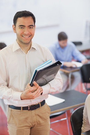 Handsome black haired teacher posing in his classroom holding some files while smiling at camera photo