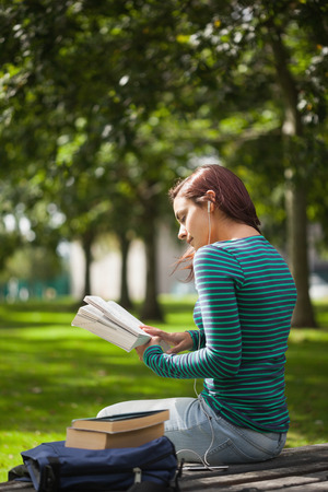 Calm casual student sitting on bench reading on campus at college photo