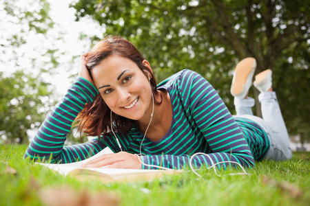 Cheerful casual student lying on grass reading a book on campus at college photo