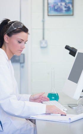 Side view of a young female researcher using computer in the laboratory photo