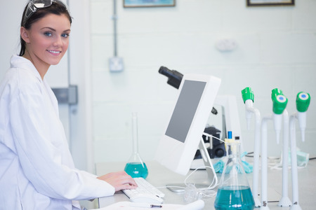 Side view portrait of a young female researcher using computer in the laboratory photo