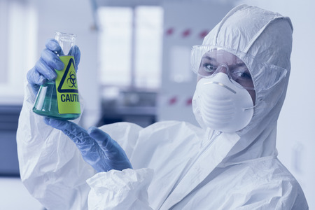 Close up portrait of a scientist in protective suit with hazardous blue chemical in flask at the laboratory photo