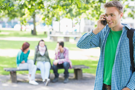 College boy using mobile phone with blurred students sitting in the park photo