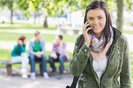 Portrait of a college girl using mobile phone with blurred students sitting in the park photo