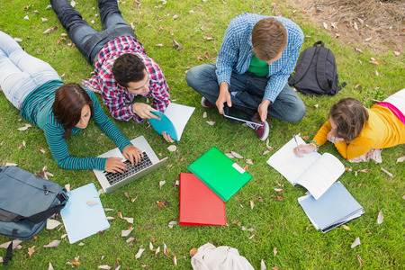 high park: High angle view of young college students using laptop while doing homework in the park