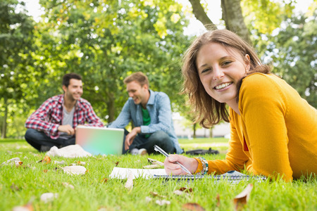 Portrait of a smiling female writing notes with two students using laptop in background at the park photo