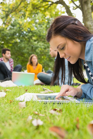 Young female using tablet PC while other students using laptop in background at the park photo