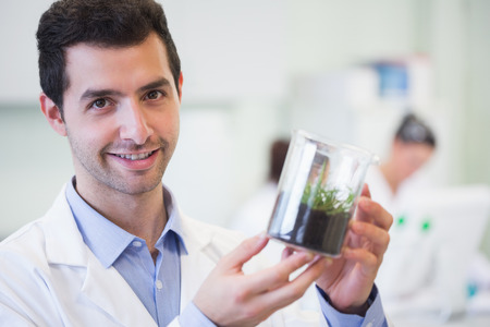 Portrait of a smiling young male researcher holding young plant at the laboratory photo